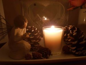 Candle fir cones and small statue praying